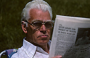 An elderly gentleman wearing tinted reading glasses holds up a broadsheet newspaper in bright sunshine at home in his garden