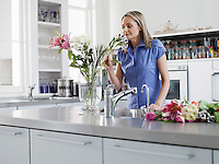 Mid adult woman in kitchen smelling flowers in vase