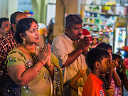 04 OCTOBER 2014 - GEORGE TOWN, PENANG, MALAYSIA: People pray as the chariot drawn by blessed oxen carries Hindu priests and the Durga deity through the streets of George Town during the Navratri procession. Navratri is a festival dedicated to the worship of the Hindu deity Durga, the most popular incarnation of Devi and one of the main forms of the Goddess Shakti in the Hindu pantheon. The word Navaratri means 'nine nights' in Sanskrit, nava meaning nine and ratri meaning nights. During these nine nights and ten days, nine forms of Shakti/Devi are worshiped.   PHOTO BY JACK KURTZ