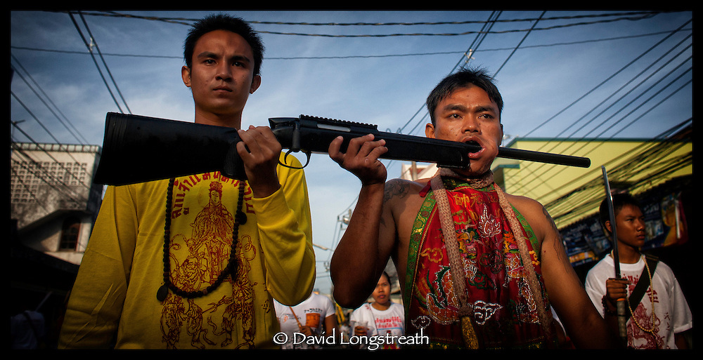 "In this ""Signature Series"" image by David Longstreath, a devotee to the Phuket, Thailand Vegetarian Festival has his face pierced by a shotgun.  he annual festival in Phuket is held on a annual basis and begins usually in late September of early October depending on the lunar cycle."