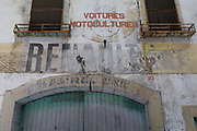 Fading garage lettering including French car manufacturer Renault, on 21st May 2017, in Fabrezan, Languedoc-Rousillon, south of France