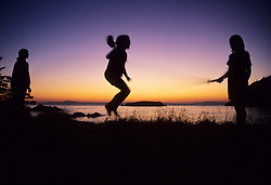 North America, United States, Washington, Whidbey Island, Silhouette of girls jumping rope near beach at sunset