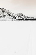 Backcountry skier crossing frozen Jenny Lake, Grand Teton National Park, Wyoming USA