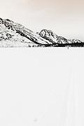 Backcountry skier crossing frozen Jenny Lake, Grand Teton National Park, Wyoming USA