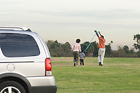 Family with one child (5-6) flying kite