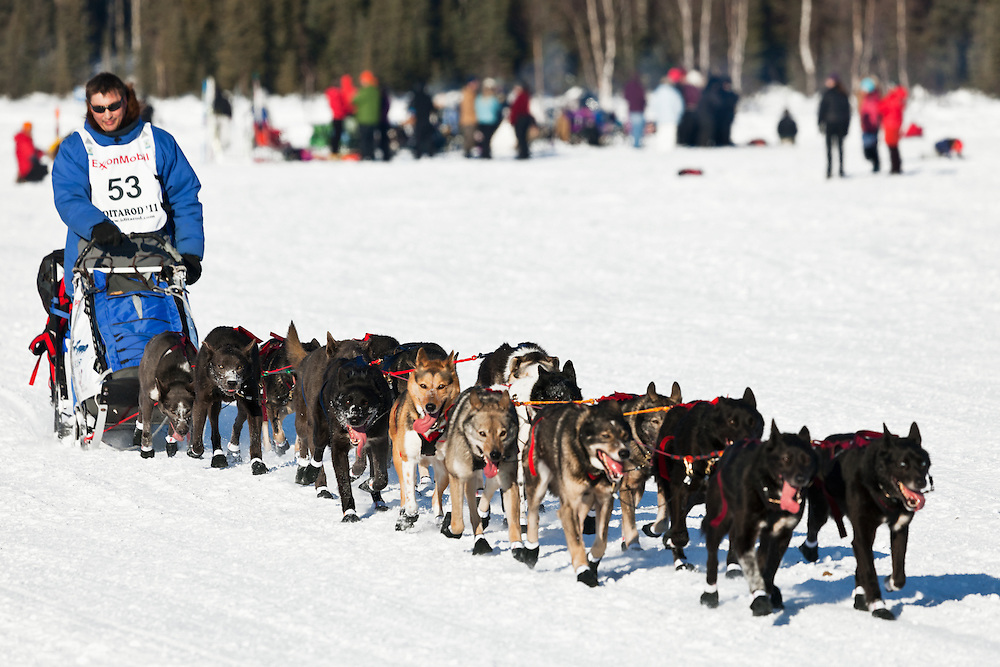 Musher John Baker competing in the 39th Iditarod Trail Sled Dog Race on Long Lake after leaving the Willow Lake area at the restart in Southcentral Alaska.  Afternoon.