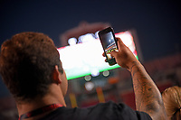NC State fan takes a photo prior to the start of a Wolfpack football game in Carter-Finley Stadium.