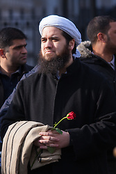 "London, February 8th 2015. Muslims demonstrate outside Downing Street  ""to denounce the uncivilised expressionists reprinting of the cartoon image of the Holy Prophet Muhammad"". PICTURED: An Iman  holds a rose symbolising love and peace."
