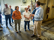 18 OCTOBER 2019 - CRAWFORDSVILLE, IOWA: US Senator AMY KLOBUCHAR (D-MN), left, and PATTY JUDGE, from Focus on Rural America, listen to ROYDON STROM, President and CEO of W2 Fuel during a tour of W2 Fuel, a biodiesel refinery that used soybeans to make biodiesel. W2 Fuel closed about a month ago because of low demand for biofuels, brought on by the number of biofuels waivers the US EPA has given to petroleum refineries. Sen. Klobuchar is on barnstorming bus tour of southeast Iowa this weekend. She is campaigning to be the Democratic nominee for the US Presidency. In addition to campaign meet and greet events, she stopped at a biofuels plant to learn about the difficulties farmers and biofuels producers face because of the trade war with China. Iowa holds the first selection event of the Presidential election cycle. The Iowa caucuses are Feb. 3, 2020.        PHOTO BY JACK KURTZ