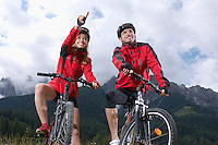 Couple on bikes in countryside woman pointing