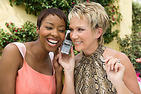 Two women using mobile phone outdoors