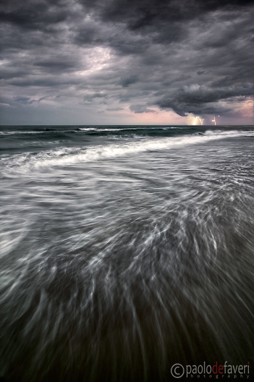 """Dark ominous skies, strong wind gusts, pouring rain and lighting bolts: a highly desirable mix of elements for a seascape of high impact. Taken at the beach of Piemanson in Camargue, France, this is a double exposure blending: 1 second for the foregorund and 10"""" for the sky."""