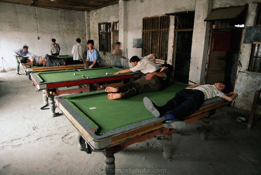Pool hall with some men sleeping on the tables. Guilin, China.