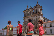 Four young Portuguese walk past the exterior of Alcobaca Monastery, Portugal.