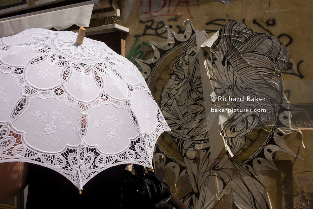 A lstreet poster for an arts event echoes the lace texture of an umbrella being used against the sun in the San Marco district of Venice, Italy.