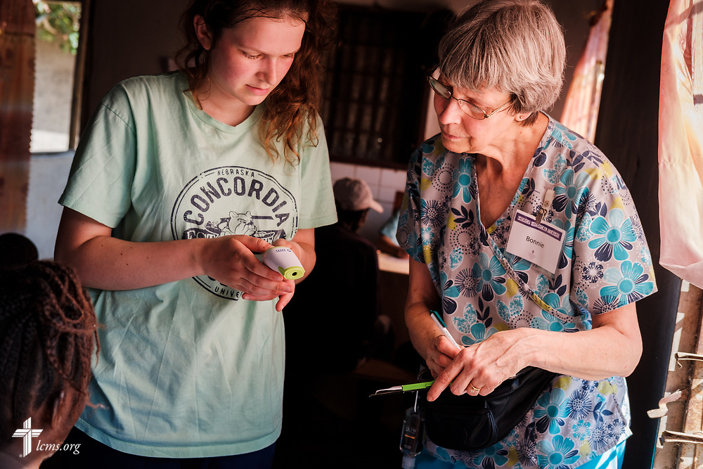 Hayden Rensner, a student at Concordia University, Nebraska, and Bonnie Hartman, a member of Faith Lutheran Church, Godfrey, Ill., work together in the vitals area of the clinic on the second day of the LCMS Mercy Medical Team on Tuesday, May 8, 2018, in the Yardu village outside Koidu, Sierra Leone, West Africa. LCMS Communications/Erik M. Lunsford
