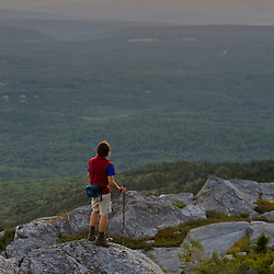 A hiker watches the sunset near the summit of Mount Monadnock in New Hampshire's Monadnock State Park.