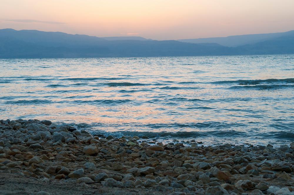 Dawn breaks on a Dead Sea beach near Ein Gedi, Israel. The land across the water is Jordan.<br /> (Dead Sea, Israel - October 2010)