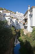 River running past whitewashed houses Setenil de las Bodegas, Cadiz province, Spain