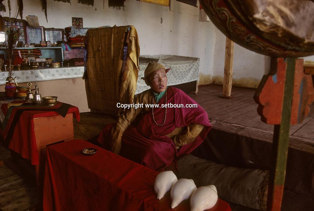 Mongolia. Pontsogtchoidlin, monastery  in a house in Ikh Tamir   /Grand Lama d'un petit temple local.Monastere maison Temple de Pontsogtchoidlin Kree, Mongolie, sum de IK TAMIR.  Le Grand Lama s'est assis à la place de haut dignitaire du temple. L'office va bientôt commencer. Devant lui, les instruments du culte sur une tablette : pichet d'eau bénite en argent surmonté de plumes de paon, tambour-sablier à boules fouettantes damaru (tib.) en forme de calottes crâniennes, clochettes à main dril-bu (tib.) ou könk avec leur 'foudre-diamant' dorj ou otchir. (dans l'aymag de ARQANGAY). /G50/123    L920726a  /  P0002577