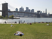 People relaxing in a public park by the Brooklyn Bridge NYC