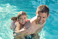 Father giving daughter piggy back in swimming pool