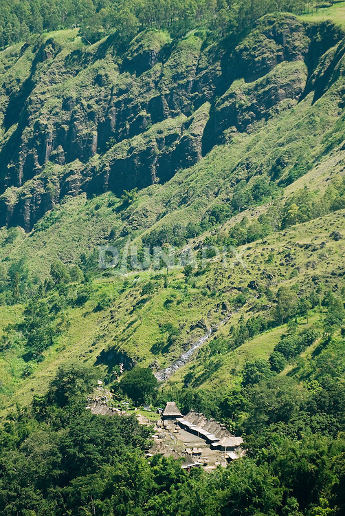 Traditional village drawfed by green mountains, Flores