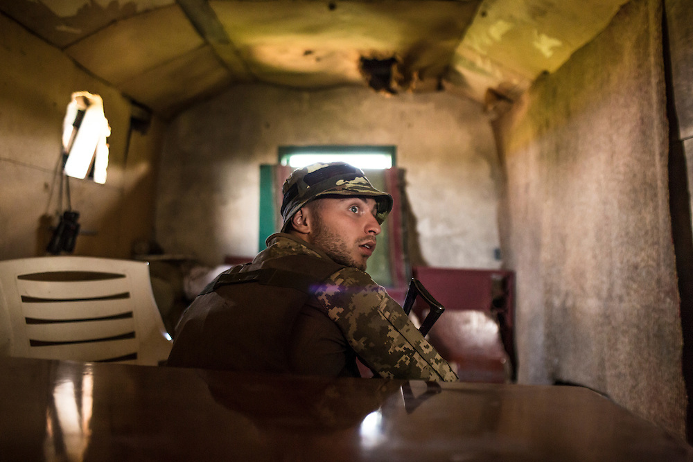 AVDIIVKA, UKRAINE - JULY 9, 2016: Lt. Denis Naumov, a Ukrainian Army press officer with the 58th brigade, in the attic of a house that was just by sniper fire in Avdiivka, Ukraine. The town is now one of the most active areas of fighting along the line of control between the Ukrainian government and Russian-backed rebels. CREDIT: Brendan Hoffman for The New York Times
