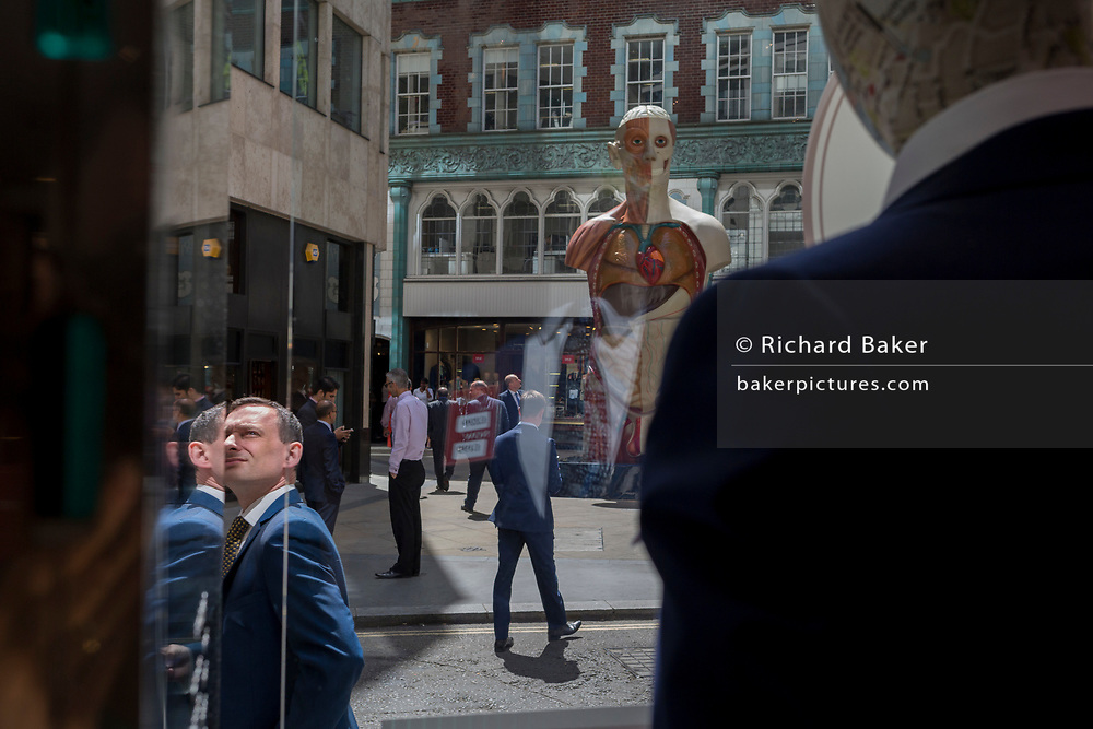 As part of the annual 'Art in the City' in the City of London, the artwork entitled Temple (2008) by Damien Hirst occupies a space opposite a menswear shop window mannequin in Lime Street in the heart of the capital's financial district, on 26th June 2017 in the City of London, England.