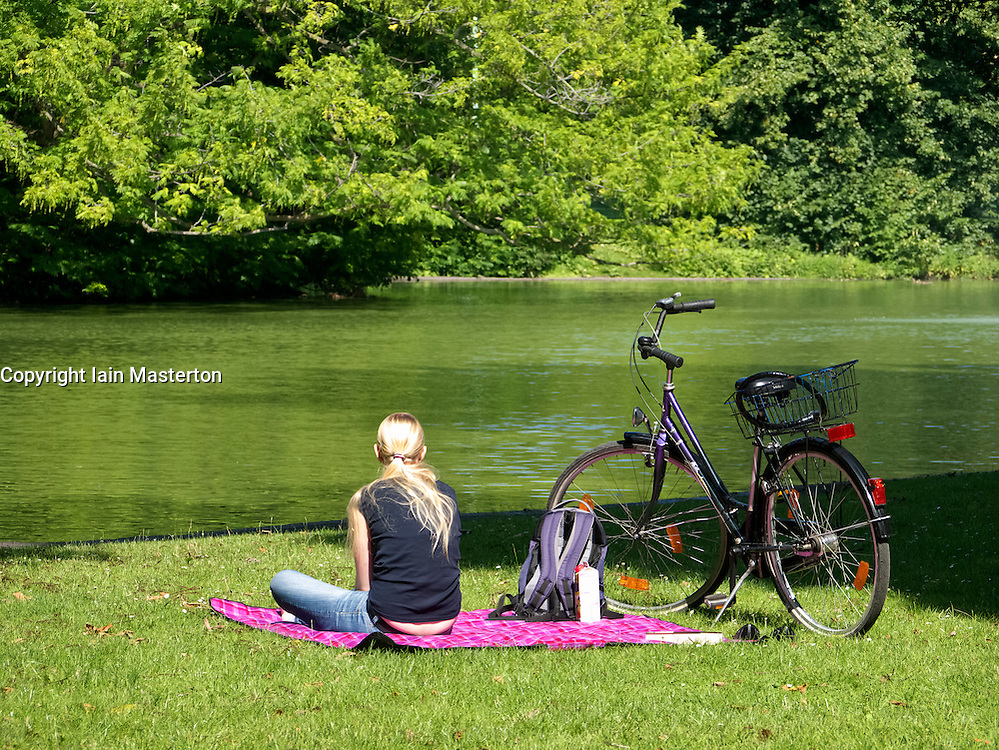 Young woman sitting beside lake in Volksgarten park in Cologne Germany