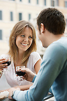 Couple sitting at outdoor cafe in Rome toasting wine glasses head and shoulders