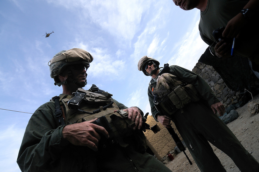 "US Marine Colonel Jeff Haynes, Commanding Officer, 201st Regional Corps Advisory Command, (left) inside a ""Qalat,"" with a OH-58 Kiowa helicopter overhead.  To his right is Marine Major Byron V. Chapman.....US mentors are living with Afghan National Army soldiers in a small ""Qalat"" rented from a nearby village in Tagab Valley.  It is part of the counterinsurgency effort to connect with villagers, gather intelligence and provide local security.....Colonel Haynes said fixating solely on the enemy is a mistake.  His men are on the sharp end of the fight taking calculated risks as COIN doctrine prescribes.  The Marines' COIN strategies come from lessons learned by the French and British as well as their own history.  During the Vietnam War the Marines employed a similar COIN idea with some success known as ""Combined Action Programs (CAP's).""  They lived in villages and fought alongside indigenous Vietnamese security forces.  Marine General Victor ""Brute"" Krulak defended the program and waged his own internal policy war with Army General Westmoreland.  Krulak lost his battle with Westmoreland who preferred massive firepower and body counts - a strategy that wreaked havoc on the civilian population.  .."