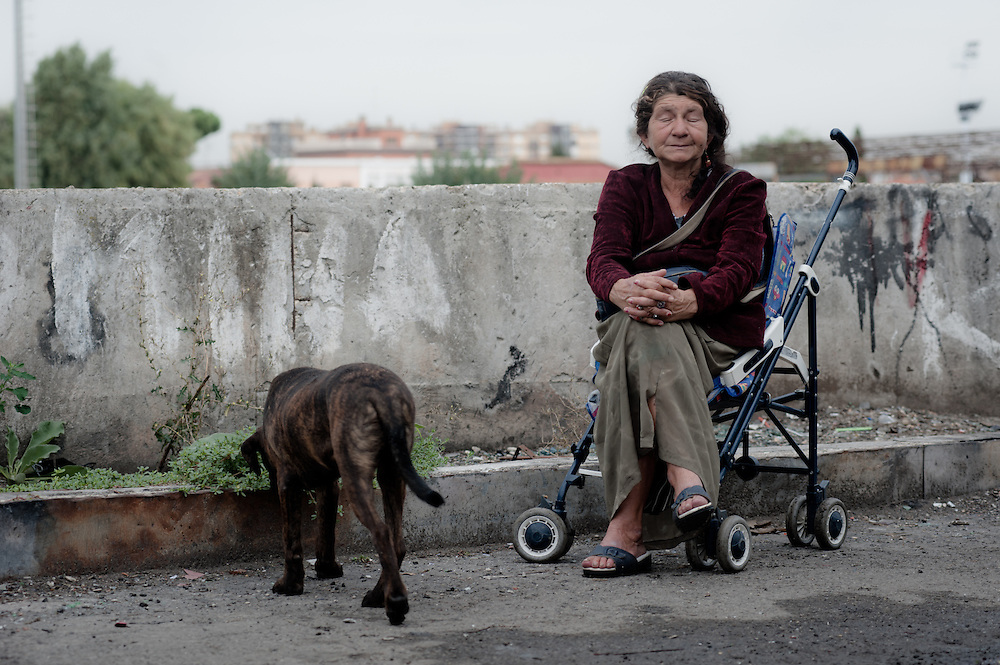 Rome, Italy - 28 September 2012: an old Bosnian woman sits on a stroller and waits in silence the caterpillars to demolish the prefabricated house she's been living in for the past 16 years. A stray dog stands undisturbed at her feet