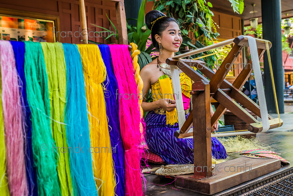 Bangkok, Thailand - December 28, 2013: woman spinning silk at Jim Thompson House museum in Bangkok, Thailand on december 28th, 2013