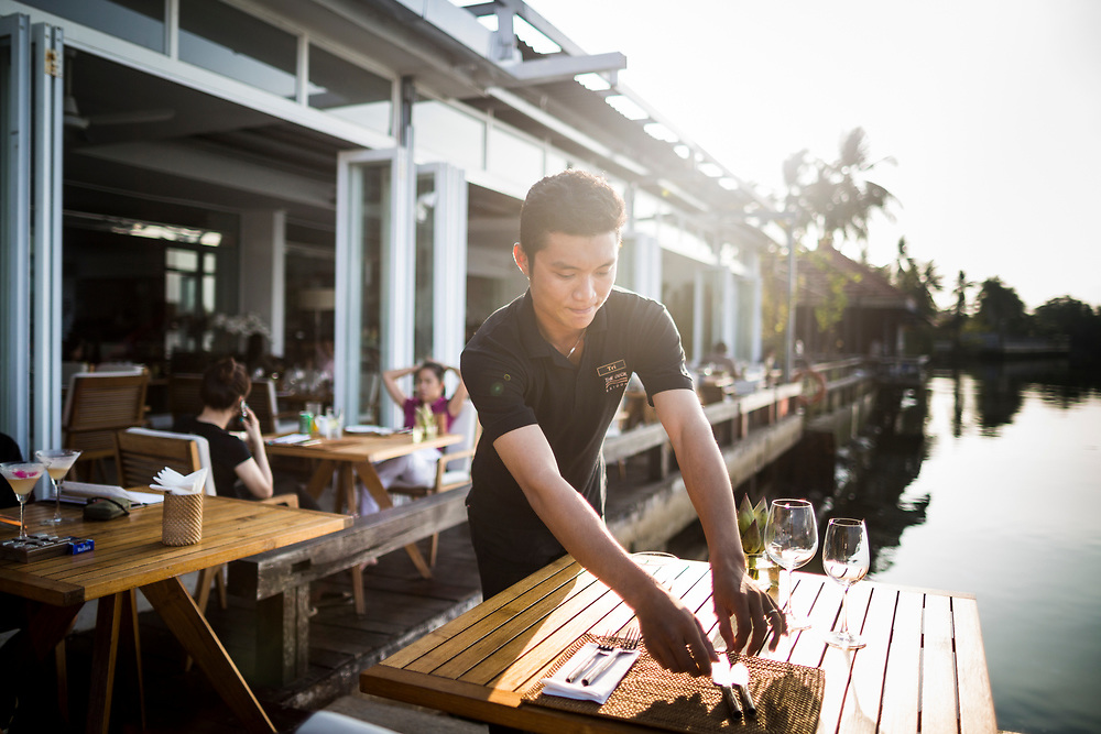 A waiter sets a table at The Deck riverside restaurant in District 2, Ho Chi Minh City, Vietnam.
