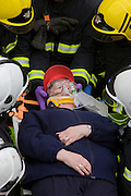 A volunteer casualty (so not reality) is rescued by medics and firefighters during a London Fire Brigade's 'extrication' team's demonstration with the Vehicle and Operator Services Agency (VOSA) on how firefighters rescue passengers by cutting open with dedicated cutting equipment a stretch limousine in London's Covent Garden Piazza. Highlighting the dangers of hiring illegal luxury or novelty cars, this vehicle was seized last year with many mechanical defects rendering it unsafe for those inside with limited exit doors. Of 358 cars stopped in March 2012, 27 were seized and 232 given prohibitions. This scenario is a simulation and therefore reproduces the reality of an emergency, using real emergency services personnel and equipment. Casualties are volunteers and none were injured in the making of this photograph.