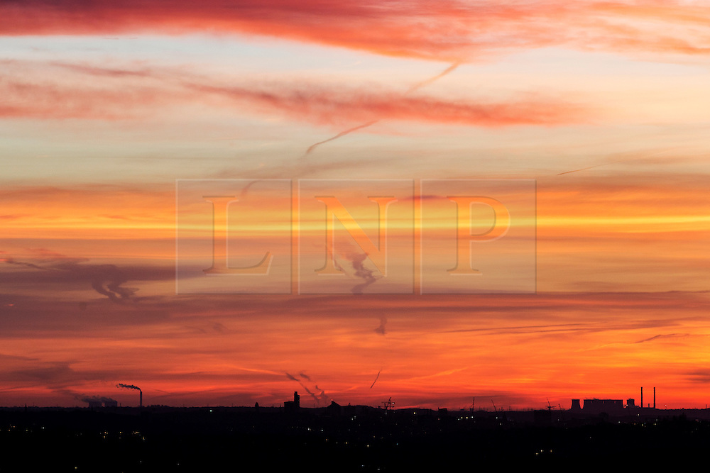 © Licensed to London News Pictures. 25/01/2016. Baildon UK. Leeds city skyline glows red in this mornings sunrise seen from Baildon Moor as Britain braces itself for more bad weather as fears grow that Storm Jonas will hit Britain. Photo credit: Andrew McCaren/LNP
