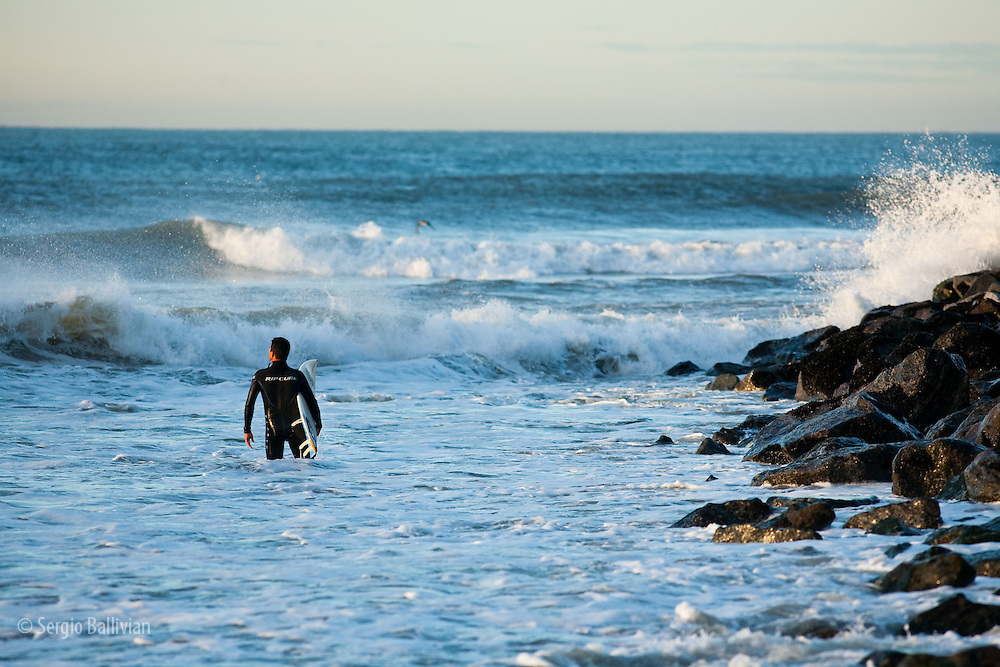 A wetsuit-clad surfer cautiously enters some rough surf near Santa Monica Beach, California in winter.