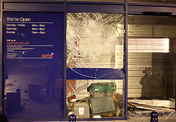 © Licensed to London News Pictures. 08/08/2011. LONDON, UK. Boxes and a smashed window are seen at the entrance to the Brixton branch of electrical store Currys.  Hundreds of rioters had previously forced their way into the shop to steal electrical goods. The looting came as violence again hit London for a second night. Photo credit: Matt Cetti-Roberts/LNP