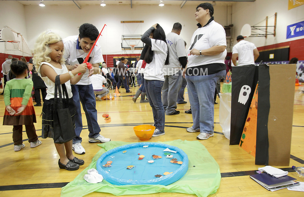 Middletown, New York - A volunteer helps a young girl wearing a costume play a fishing game at the Family Fall Festival at the Middletown YMCA on Oct. 23, 2010.