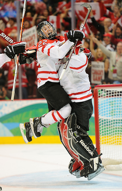 Team Canada captain Haley Wickenheiser jumps on goalie Shannon Szabados  after beating The United States to win the gold medal in hockey at Canada Hockey Place, day 14 of the 2010 Vancouver Winter Olympics.