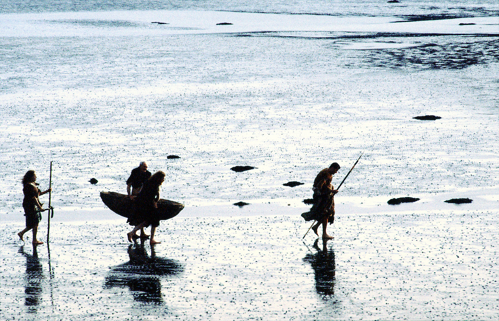 Neolithic prehistoric cave men caveman cavemen man walking on mudflats seashore carrying skin boat coracle curragh and spears