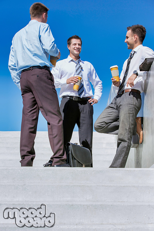 Group of businessmen standing and talking while drinking coffee during break