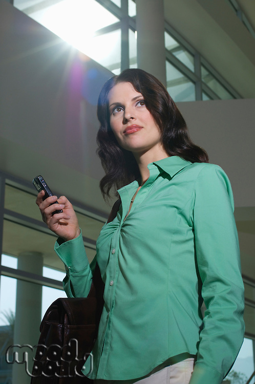 Business woman using mobile phone standing in office building