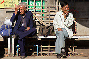 Two gentleman await the bus in Pai, Thailand.