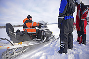 Antti, young Finnish guide from VisitInari, explains how to ride a snowmobile in the wilderness of Inari, Lapland, Finland