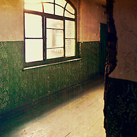 An abandoned place with big window with the sun behind the glass. Daytime but creepy. Indoor.