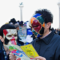 VENICE, ITALY - FEBRUARY 19:  Tourist  wearing Venetian masks check the program of the 2011 Carnival in St Mark Square ahead of the opening ceremony on February 19, 2011 in Venice, Italy. The fountain pouring wine features today during the Gran brindisi a Venezia or Grand Toast in Venicethe opening ceremony of this year Carnival .