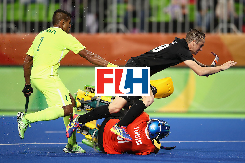 RIO DE JANEIRO, BRAZIL - AUGUST 10:  Bruno Mendonca of Brazil watches on as Hugo Inglis of New Zealand is tackled by the Brazil goal keeper Rodrigo Faustino during the men's pool A match between New Zealand and Brazil on Day 5 of the Rio 2016 Olympic Games at the Olympic Hockey Centre on August 10, 2016 in Rio de Janeiro, Brazil.  (Photo by Mark Kolbe/Getty Images)