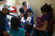 Sarah Crawford a volunteer registered nurse communicates through the use of a translator with an indigenous family during a health screening clinic. Worthy Village provides health clinics, education and economic opportunities throughout the Solola region of Guatemala.